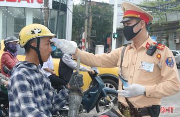 Người đi đường ở TP Hà Tĩnh ngỡ ngàng khi được CSGT đo thân nhiệt, phát khẩu trang miễn phí